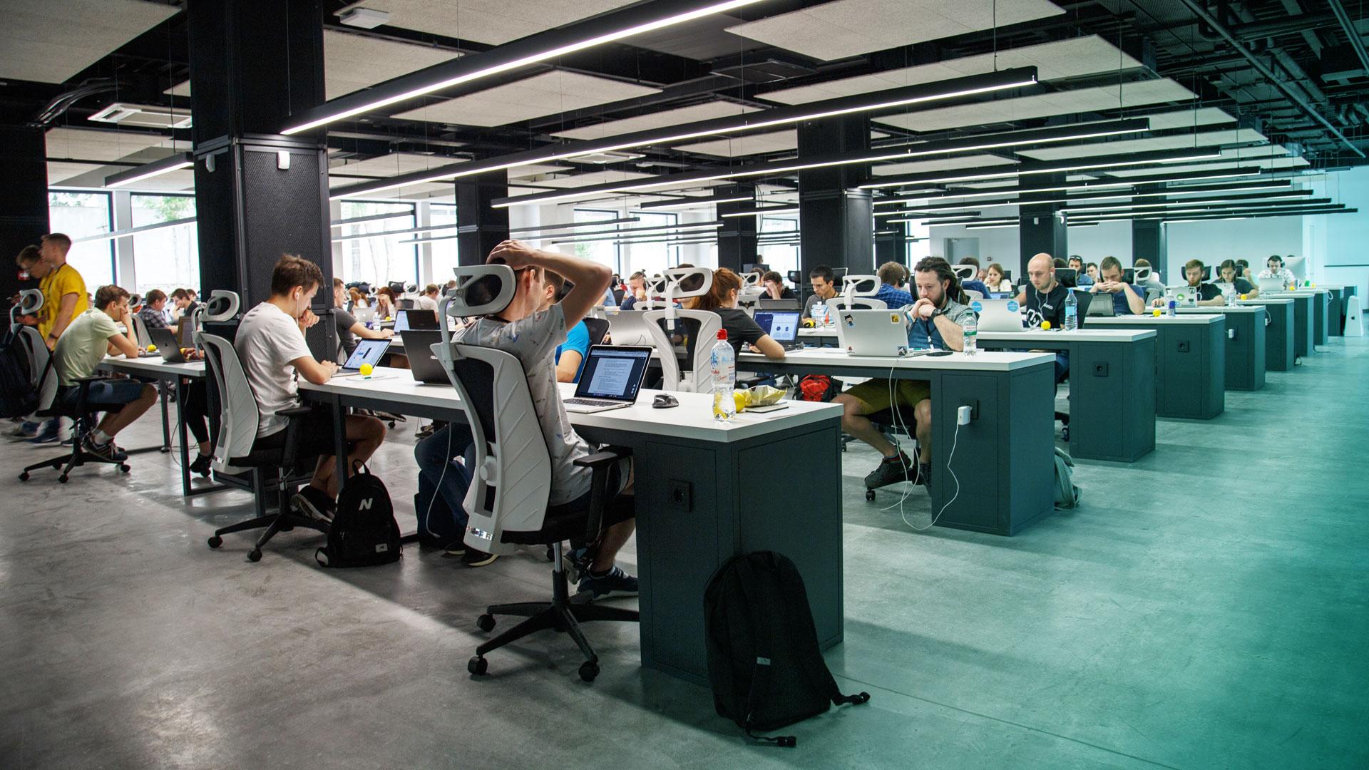 Et rom fylt av mange kontorplasser og mennesker