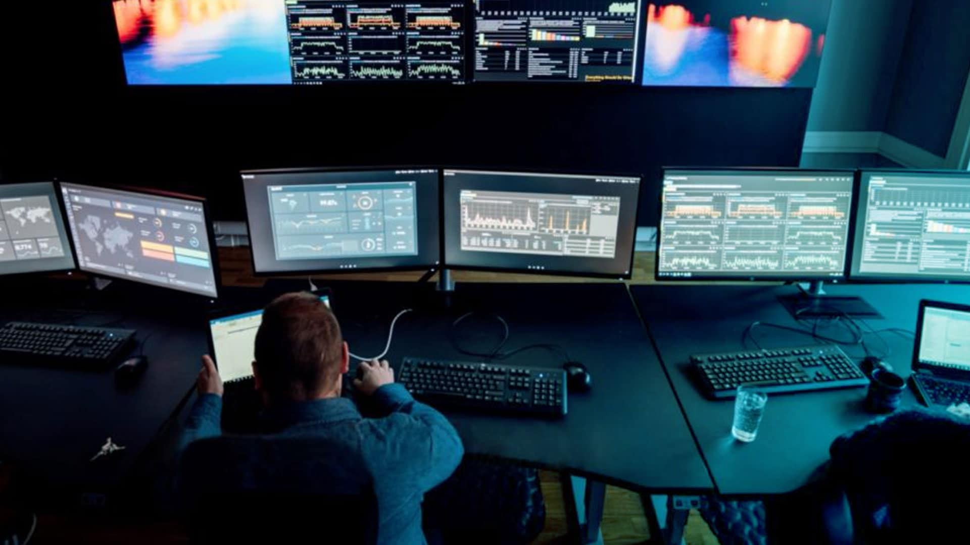 En mann kontrollerer mange skjermer i et sort rom