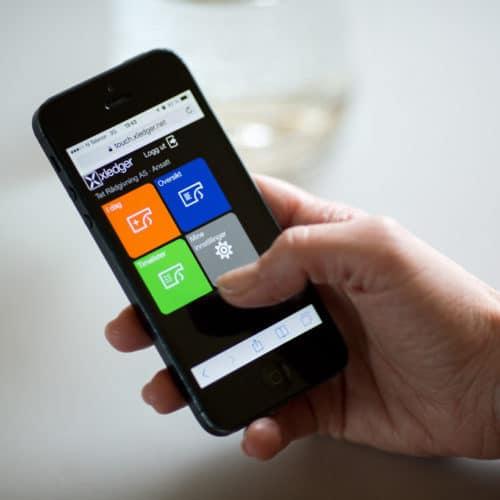 Smarttelefon med systemet Xledger på skjermen