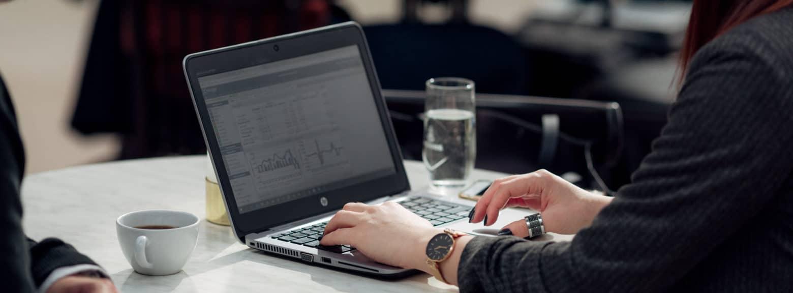 Nærbilde av kvinne som taster på en laptop i et møte