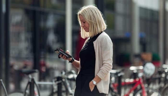 Blond kvinne ser på mobil utendørs