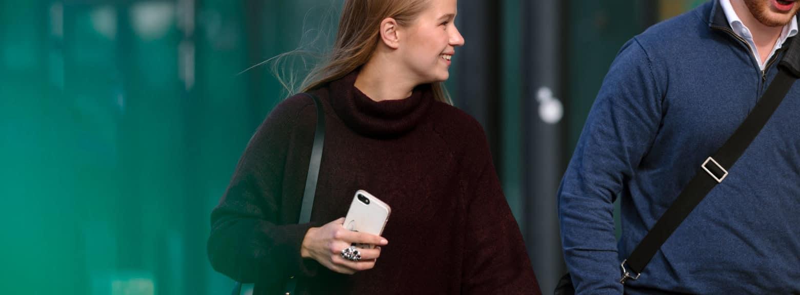 Ung kvinne med smarttelefon snakker med ung mann