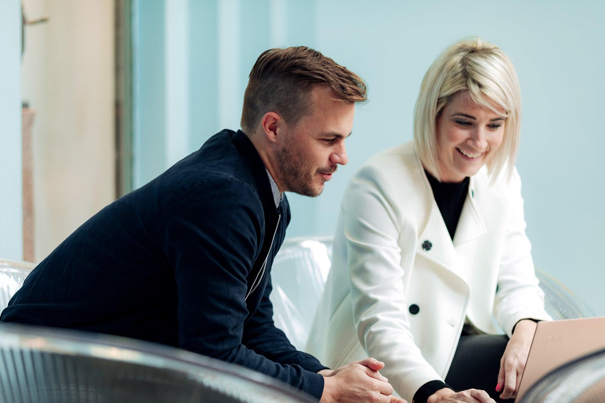 Mann og dame ser på pc-skjerm og smiler