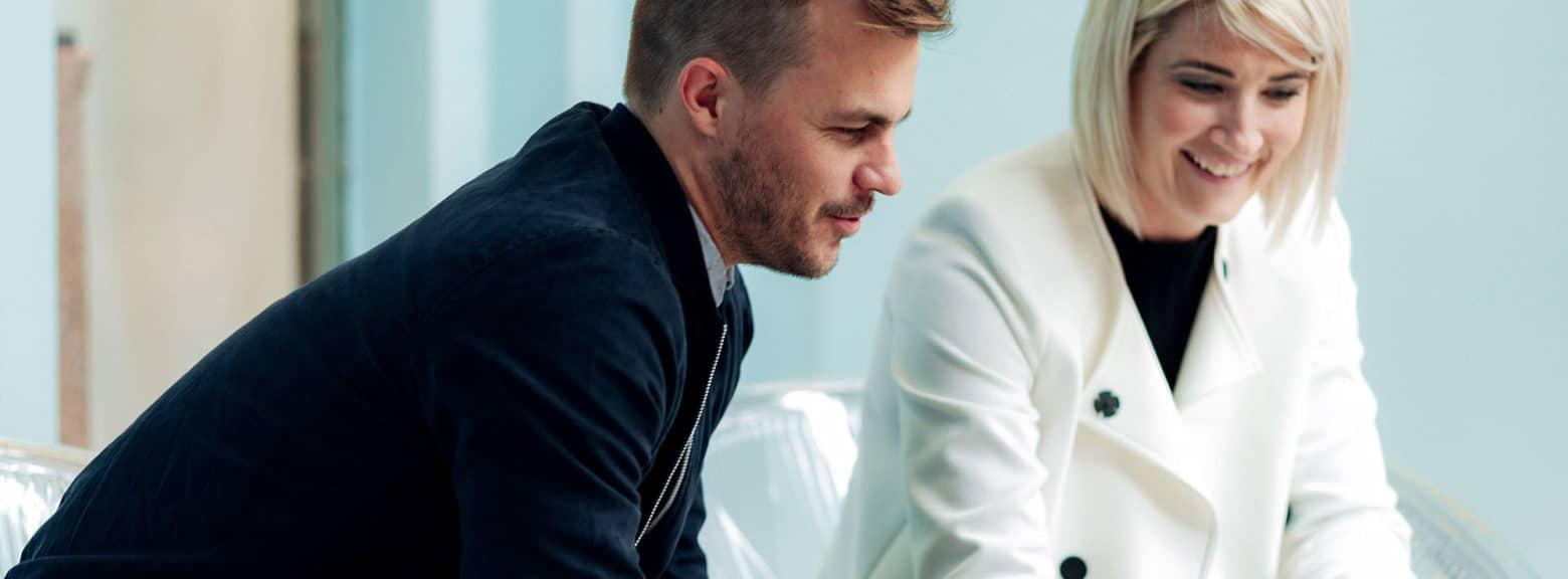 Ung kvinne og ung mann i samtale på kontor