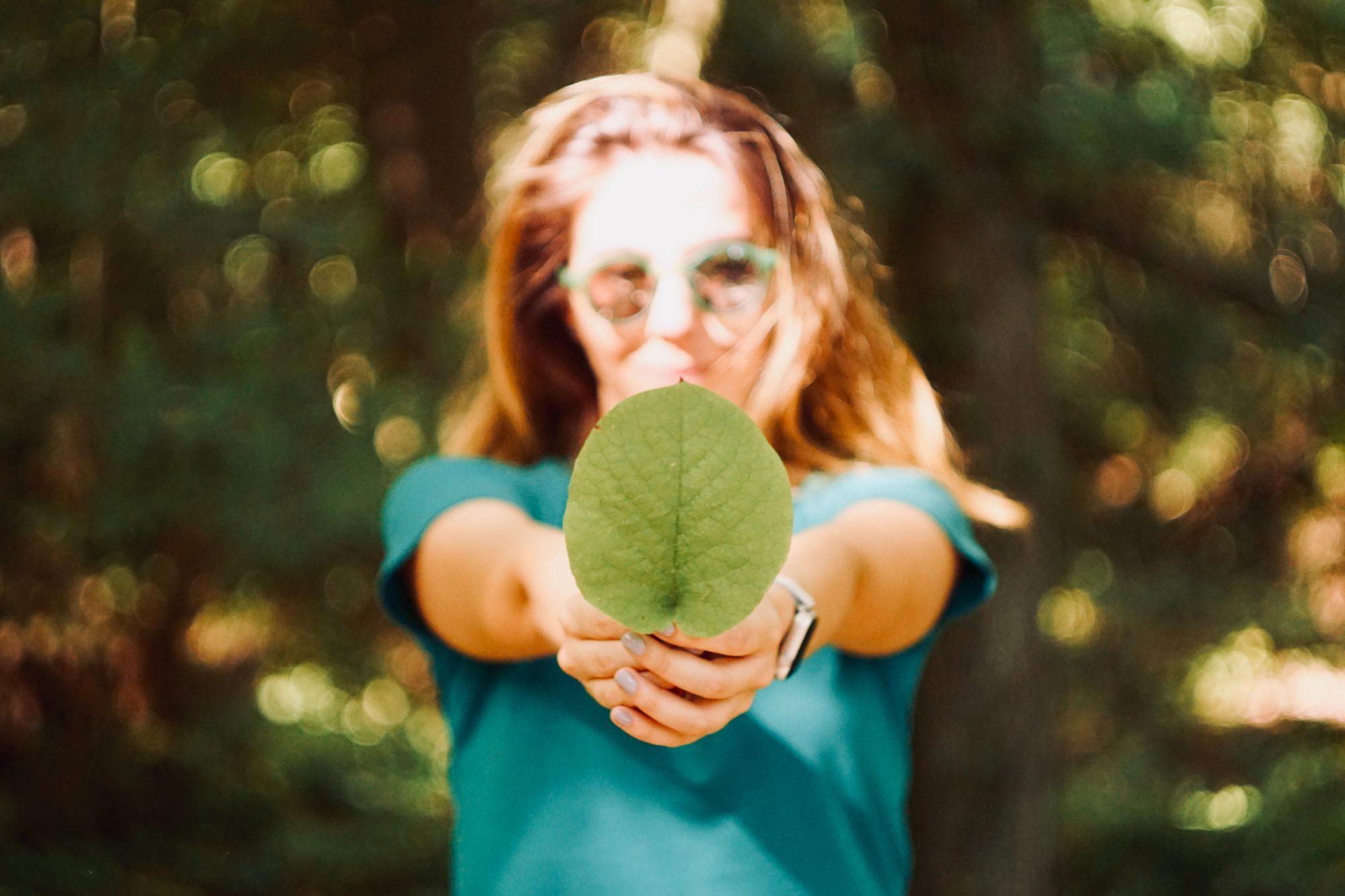 Kvinne med grønt blad i hendene
