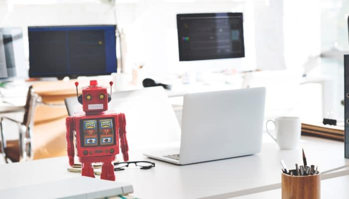 Hvitt kontorlandskap med en rød plastikkrobot