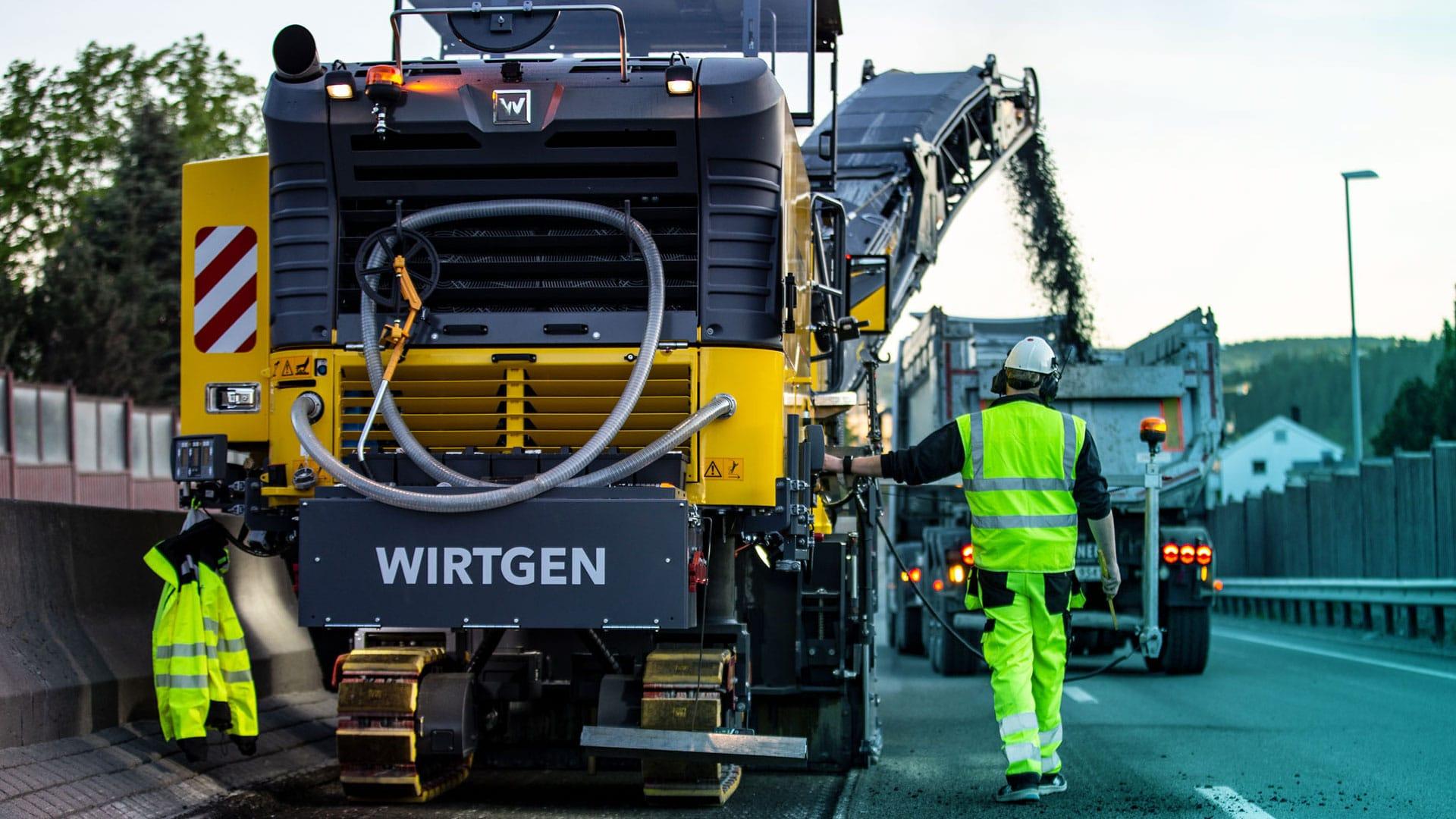 En mann kontrollerer en asfaltleggende maskin