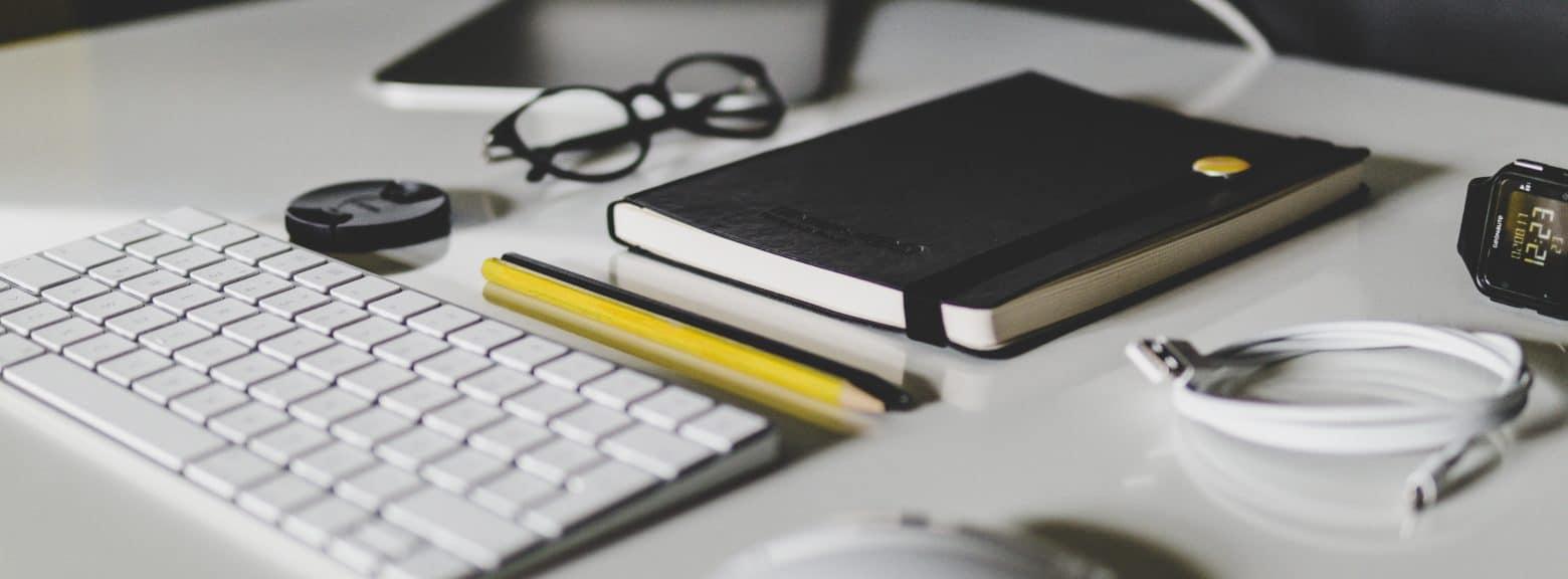Detalj av tastatur og kontorrekvisita på en pult