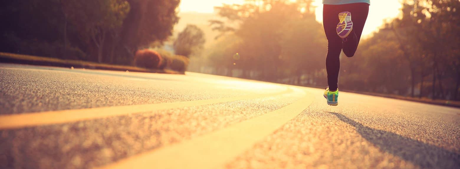Dame løper på asfalt mot sol