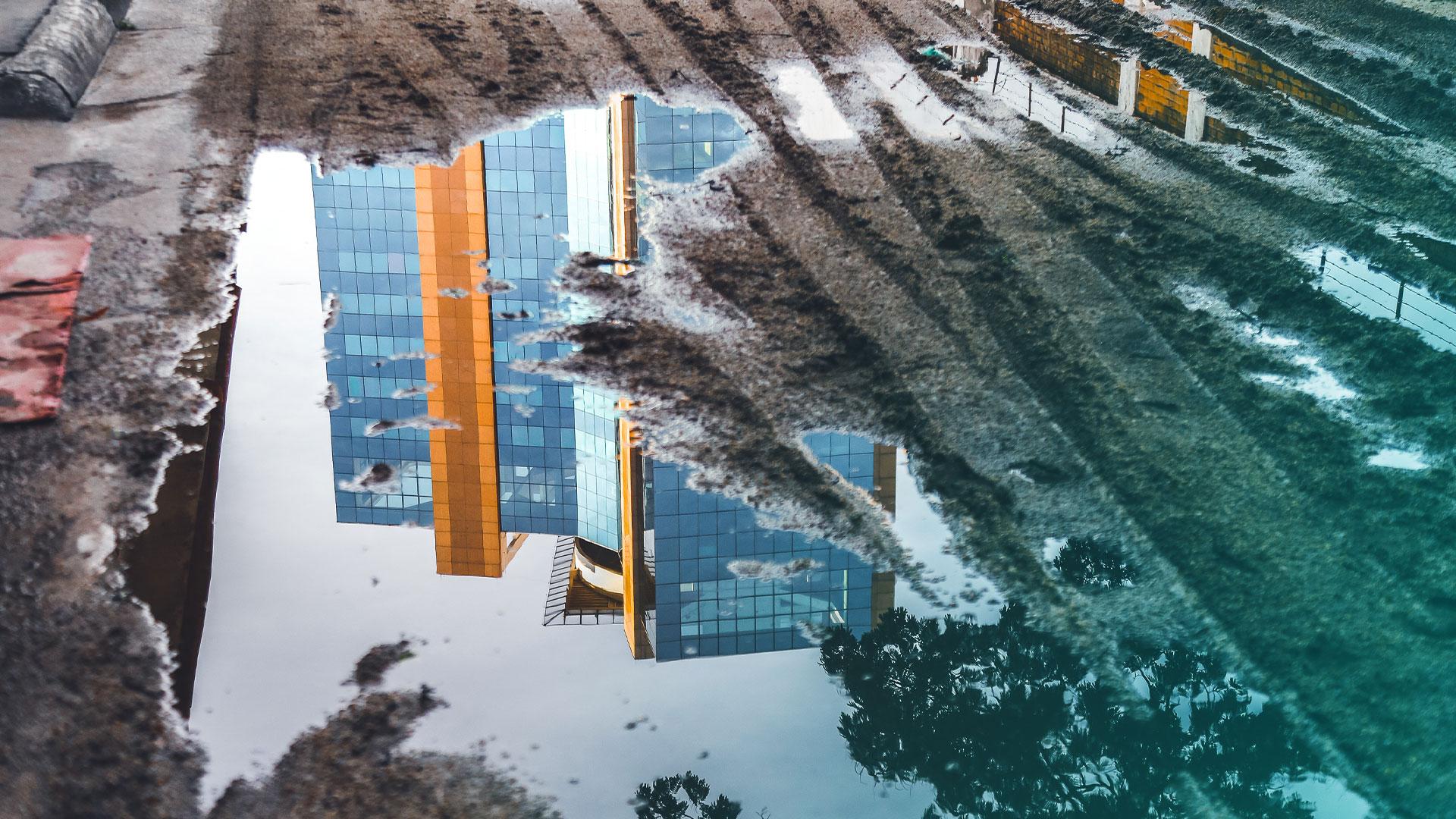Et kontorbygg speilser seg i en sølepytt