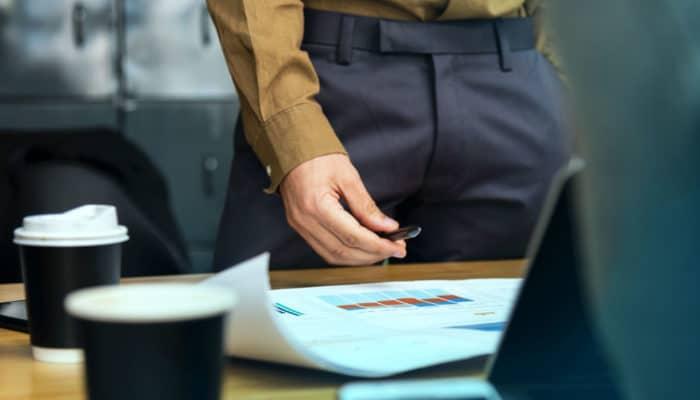 Mannshånd holder en penn mot statistikk