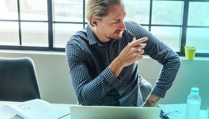 Mann ved laptop peker mot kollega